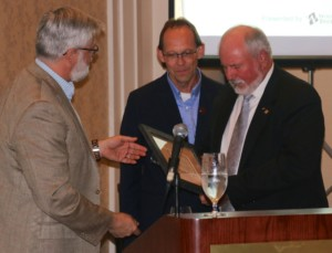 Image of Kerry DePape and Larry White, both of the Architectural Woodwork Manufacturers Association of Canada, presenting a plaque to Rob Gustafson