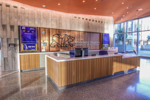 """A wood panelled reception area with a sign: """"Associated Students University of California"""""""