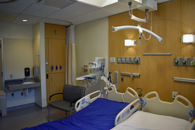 Image of hospital room with wood paneled equipment wall and cabinet.