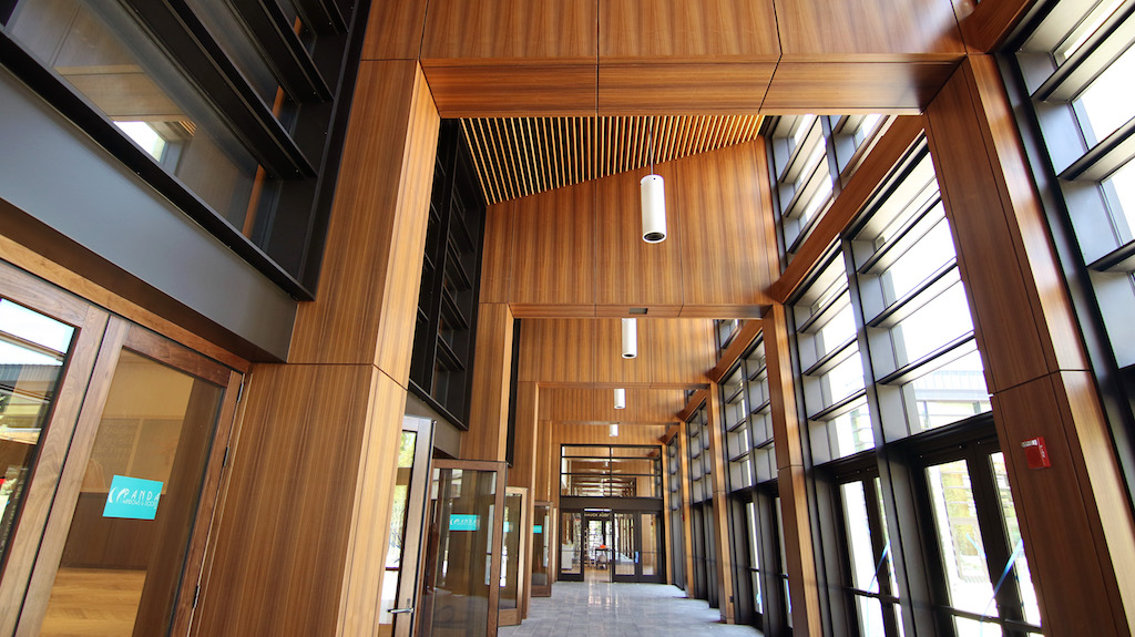 Image of hallway showing wood paneled walls between windows and a wood slat ceiling.