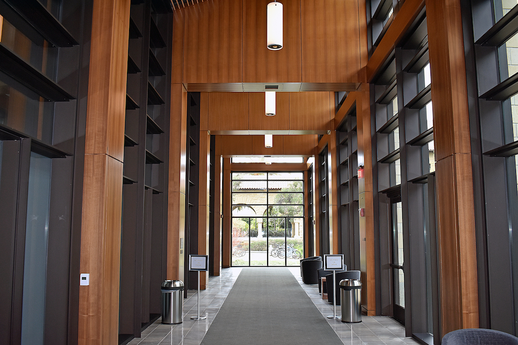 Image of hallway with wood paneled sections between windows.