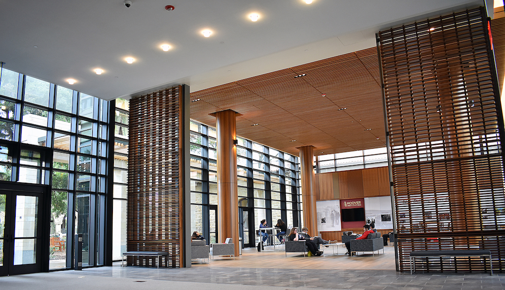 Image of lobby with wood paneled walls, columns, and ceiling with wood slat dividers.
