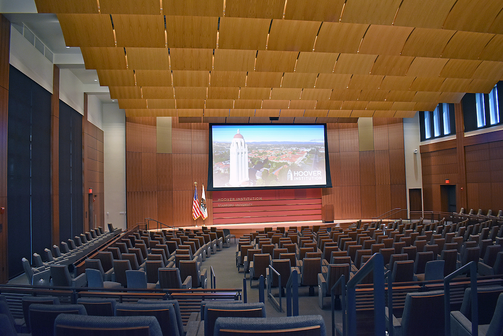 Image of auditorium with wood paneled walls, columns, and ceiling, with wood dividers between sections..