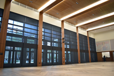 Image of wall of windows with wood paneled columns and ceiling with shades down.